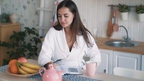 De jonge vrouw zit op keuken, maakt nota's in notitieboekje dan weg kijkt, langzame motie stock video