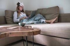 De jonge vrouw zit op de laag en werkt aan haar laptop stock foto's