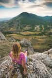 De jonge vrouw zit op de rand van de rotsachtige klip Royalty-vrije Stock Afbeeldingen