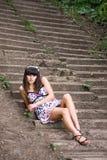 De jonge vrouw zit op treden Stock Foto's