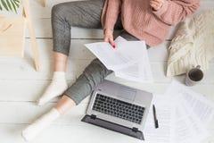 De jonge vrouw zit op de vloer in een Skandinavisch flatbinnenland met laptop, bestuderend wet, freelance meisje op het werk stock afbeeldingen