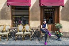 De jonge vrouw zit voor de koffie Stock Fotografie