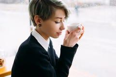 De jonge vrouw zit de vrije tijd van de de kopkoffie van de koffiegreep Stock Afbeeldingen