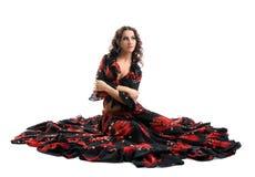 De jonge vrouw zit in zigeuner zwart en rood kostuum Stock Foto