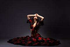 De jonge vrouw zit in zigeuner zwart en rood kostuum Stock Afbeelding