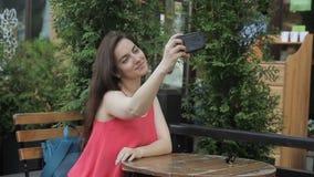 De jonge vrouw in de zomerkoffie bij lijst maakt foto op telefoon stock videobeelden