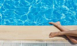 De jonge vrouw zonnebaadt dichtbij een turkoois zwembad op een zonnige dag royalty-vrije stock afbeelding