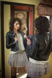 De jonge vrouw in zwart leerjasje en de grijze korte tutu begrenzen het onderzoeken van een grote spiegel Het mooie krullende don Royalty-vrije Stock Foto