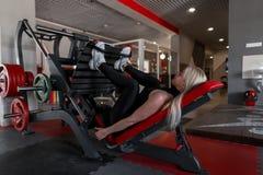 De jonge vrouw in zwarte kleren in tennisschoenen doet oefeningen die voor benen op een moderne simulator in de gymnastiek liggen royalty-vrije stock fotografie