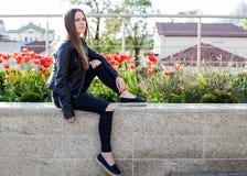 De jonge vrouw in zwarte laag en jeans zit op de steenverschansing Stock Foto's