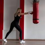 De jonge vrouw in zwarte sportkleding in modieuze tennisschoenen in rode bokshandschoenen slaat een ponsenzak in een moderne gymn stock fotografie