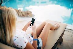 De jonge vrouw in zwempak het ontspannen op chaise zitkamer en gebruikt haar telefoon voor het texting stock foto's