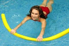 De jonge vrouw zwemt met noedel stock fotografie