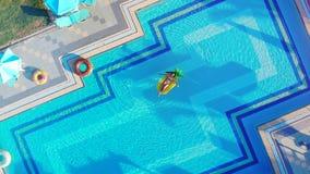 De jonge vrouw zwemt op een matras in een pool stock footage