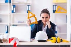De jonge vrouwelijke architect die in het bureau werken stock afbeeldingen