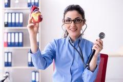 De jonge vrouwelijke arts die in de kliniek werken stock foto's