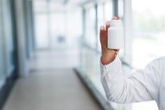 De jonge vrouwelijke arts houdt lege fles royalty-vrije stock foto