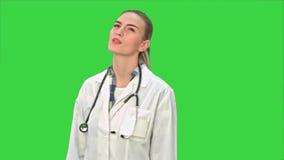 De jonge vrouwelijke arts vermoeide, geeuwend en lijdend aan hoofdpijn op het Groen Scherm, Chromasleutel stock video