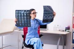 De jonge vrouwelijke artsenradioloog die in de kliniek werken stock afbeelding