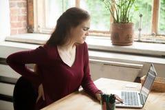 De jonge vrouwelijke beambte heeft achterongemak bij het werkbureau stock afbeelding