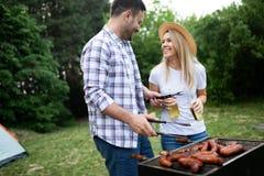 De jonge vrouwelijke en mannelijke barbecue van het paarbaksel in aard stock afbeelding