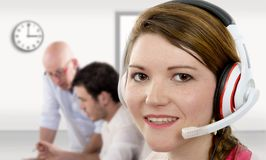De jonge vrouwelijke exploitant van de steuntelefoon in hoofdtelefoon Stock Afbeelding
