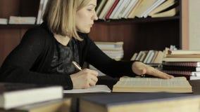 De jonge vrouwelijke gediplomeerde treft voor een lezing voorbereidingen, zittend bij het bureau en schrijft de noodzakelijke inf stock video