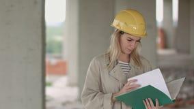 De jonge vrouwelijke ingenieur van de architectenbouw bij een bouwwerf eximaining documenten stock videobeelden