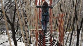 De jonge vrouwelijke klimmer loopt door de brug van de tegenhangerkabel op hoge kabelscursus in extreem park Bergbeklimmingsconce stock videobeelden