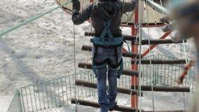 De jonge vrouwelijke klimmer loopt door de brug van de tegenhangerkabel op hoge kabelscursus in extreem park Bergbeklimmingsconce stock footage