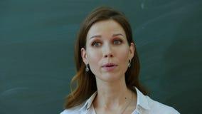 De jonge vrouwelijke leraar vertelt het interesseren aan klasse dichtbij het bord stock afbeeldingen