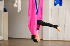De jonge vrouwelijke persoon het praktizeren positie van de inversie anti-gravity yoga Royalty-vrije Stock Afbeeldingen