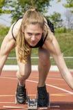 De jonge vrouwelijke positie van het atletenbegin royalty-vrije stock foto