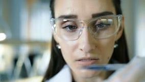 De jonge vrouwelijke reageerbuis van de wetenschapperholding met vloeibare steekproef die onderzoek naar klinisch laboratorium ma stock video