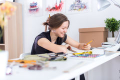 De jonge vrouwelijke schets die van de kunstenaarstekening sketchbook met potlood bij haar werkplaats in studio gebruiken Zijaanz Royalty-vrije Stock Foto