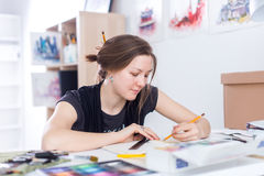 De jonge vrouwelijke schets die van de kunstenaarstekening sketchbook met potlood bij haar werkplaats in studio gebruiken Zijaanz royalty-vrije stock afbeeldingen