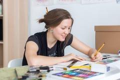 De jonge vrouwelijke schets die van de kunstenaarstekening sketchbook met potlood bij haar werkplaats in studio gebruiken Zijaanz royalty-vrije stock foto's
