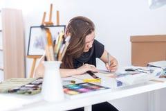 De jonge vrouwelijke schets die van de kunstenaarstekening sketchbook met potlood bij haar werkplaats in studio gebruiken Zijaanz stock foto