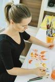 De jonge vrouwelijke schets van de kunstenaarstekening bij haar werkplaats in studio stock foto's