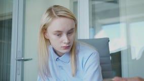 De jonge vrouwelijke secretaresse raakt haar blond haar terwijl het krijgen terugkoppelt van haar werkgever stock video