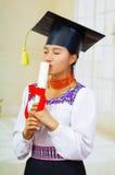 De jonge vrouwelijke student die traditionele blouse en graduatiehoed, het houden dragen rolde diploma op, die ogen het kussen sl Royalty-vrije Stock Afbeelding