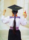 De jonge vrouwelijke student die traditionele blouse en graduatiehoed, het houden dragen rolde diploma op, rug die camera onder o Royalty-vrije Stock Foto