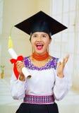 De jonge vrouwelijke student die traditionele blouse en graduatiehoed, het houden dragen rolde diploma op, trots glimlachend voor Royalty-vrije Stock Afbeelding