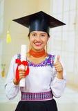 De jonge vrouwelijke student die traditionele blouse en graduatiehoed, het houden dragen rolde diploma op, trots glimlachend voor Royalty-vrije Stock Foto