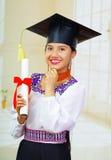 De jonge vrouwelijke student die traditionele blouse en graduatiehoed, het houden dragen rolde diploma op, trots glimlachend voor Royalty-vrije Stock Foto's