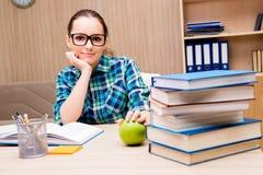 De jonge vrouwelijke student die voor examens voorbereidingen treffen stock foto
