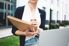De jonge vrouwelijke student treft voorbereidingen want het onderzoekswerk in openlucht in stedelijke ruimte tegenover universite royalty-vrije stock foto