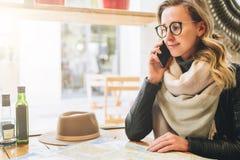De jonge vrouwelijke toerist zit in koffie bij lijst en spreekt op celtelefoon Het meisje roept haar vriend Toerisme, reis Stock Foto