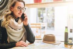 De jonge vrouwelijke toerist zit in koffie bij lijst en spreekt op celtelefoon Het meisje roept haar vriend Toerisme, reis Stock Afbeelding