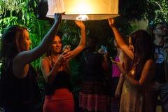 De jonge vrouwelijke toeristen geven een drijvende lantaarn in Chiang Mai vrij, Royalty-vrije Stock Foto